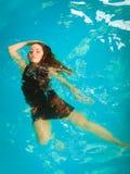 Relajación flotante de la mujer en agua de la piscina Fotografía de archivo