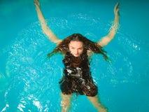 Relajación flotante de la mujer en agua de la piscina Imágenes de archivo libres de regalías