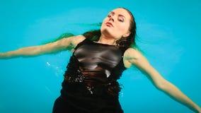 Relajación flotante de la mujer en agua de la piscina Fotografía de archivo libre de regalías