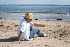 Relajación madura del hombre, jugando con la arena en la playa Foto de archivo libre de regalías