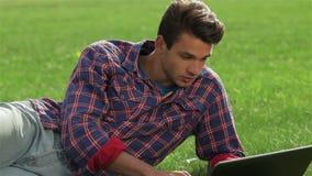 Relajación masculina en su jardín usando el ordenador portátil almacen de metraje de vídeo