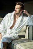 Relajación masculina joven, muscular, hermosa, sana en un sofá en a fotos de archivo libres de regalías