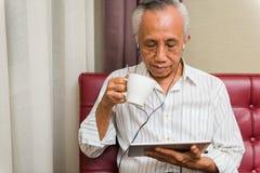 Relajación mayor asiática con la tableta y la bebida fotografía de archivo