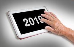 Relajación mayor y su tableta - 2019 de la señora Foto de archivo libre de regalías