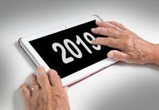 Relajación mayor y su tableta - 2019 de la señora Fotos de archivo