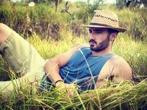 Relajación modelo masculina, poniendo en un campo foto de archivo