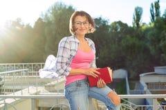 Relajación morena sonriente al aire libre y libro de lectura Fotos de archivo libres de regalías
