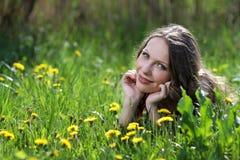 Relajación sonriente bonita de la muchacha al aire libre en flores Imagenes de archivo