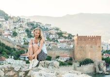Relajación turística de la mujer rubia joven en la pared antigua de la fortaleza del castillo de Alanya Kizil Kule o torre roja e fotografía de archivo