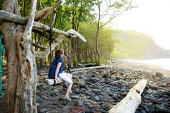 Relajación turística femenina joven en un oscilación hecho a mano en la playa rocosa del valle de Pololu en la isla grande de Haw Fotografía de archivo libre de regalías