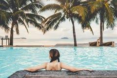Relajaci?n despreocupada de la mujer en concepto de las vacaciones de verano de la piscina foto de archivo