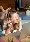 Relajación con el vidrio de vino en el ordenador portátil Foto de archivo