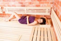 Relajación femenina joven hermosa en sauna y mentira en banco Fotografía de archivo libre de regalías