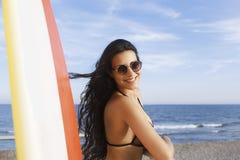 Relajación femenina latina feliz después de practicar surf en el océano durante su tiempo de la reconstrucción Imagen de archivo libre de regalías
