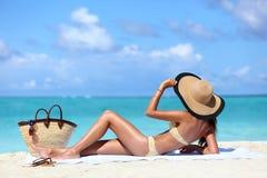 Relajación que broncea del sombrero de la mujer atractiva del bikini en la playa Fotos de archivo
