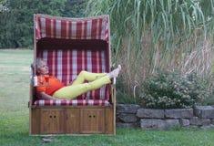 Relajada, la mujer atractiva miente en la silla de playa de mimbre cubierta y disfruta del día de fiesta imagen de archivo