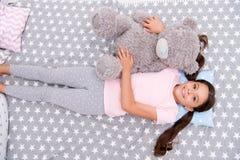 Relaje el concepto La niña se relaja en cama El niño lindo se relaja con el juguete del oso de peluche Relaje y disfrute de la vi imagen de archivo