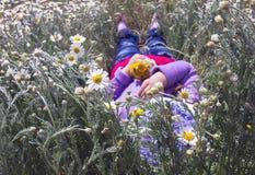 Relaje a la muchacha en un campo de margaritas con un ramo de flores Foto de archivo