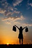 Relaje a la mujer que sostiene los panieres en silueta de la puesta del sol Fotos de archivo