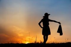 Relaje a la mujer que sostiene los panieres en silueta de la puesta del sol Imagenes de archivo