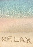 Relaje la palabra escrita en la arena, en una playa hermosa con las ondas azules claras en fondo Imagen de archivo libre de regalías