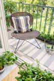 Relaje la zona en un balcón con una silla, una manta y plantas imagen de archivo libre de regalías