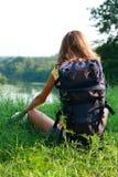 Relaje a las hojas de ruta (traveler) de la mujer que se sientan en la hierba Fotografía de archivo libre de regalías