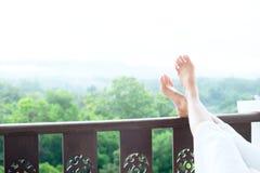 Relaje a los pies de la mujer joven que mienten en el colchón suave fotos de archivo libres de regalías