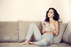 Relaje pensativo en la mujer adolescente del sofá con la taza Fotografía de archivo