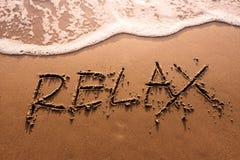 Relaksu pojęcie, Relaksuje słowo Pisać na lato piaska plaży z Zdjęcia Stock