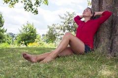 Relaksująca młoda kobieta cieszy się lato świeżość pod drzewem obraz stock