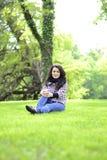 Relaksująca natura - piękny zdrowy kobiety obsiadanie na trawie Obraz Stock