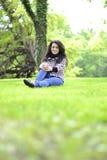 Relaksująca natura - piękny zdrowy kobiety obsiadanie na trawie Zdjęcie Royalty Free