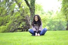 Relaksująca natura - piękny zdrowy kobiety obsiadanie na trawie Fotografia Royalty Free