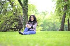 Relaksująca natura - piękny zdrowy kobiety obsiadanie na trawie Fotografia Stock