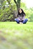 Relaksująca natura - piękny zdrowy kobiety obsiadanie na trawie Obrazy Stock
