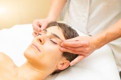 Relaksujący estetyczny masaż dla młodej kobiety z twarzą z oko remisem zdjęcia royalty free