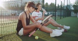 Relaksuje czas po tenisowych gry dwa młodych dam chłodzi siedzącego puszek na podłoga przy tenisowym sądem, woda pitna, jeden zbiory wideo