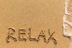 Relaksuje - formułuje patroszonego na piasek plaży Zdjęcie Royalty Free