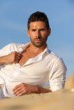 Relalaxed Mann gesetzt auf dem Sand Stockfoto
