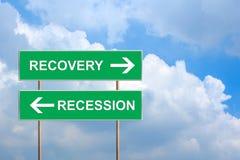 Relance et récession sur le panneau routier vert Photo stock