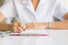 Relatório da escrita da enfermeira no hospital fotografia de stock