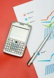 Relatório da finança com uma pena e um móbil Fotografia de Stock Royalty Free