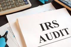 Relatório de auditoria e calculadora do IRS em uma mesa imagens de stock