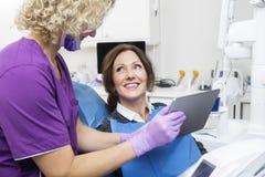 Relatório mostrando assistente ao paciente feliz na tabuleta de Digitas foto de stock