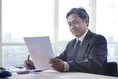 Relatório superior do papel de negócio da leitura do homem de funcionamento no tabl de trabalho Fotos de Stock Royalty Free