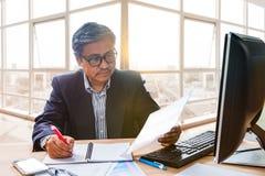 Relatório superior do papel de negócio da leitura do homem de funcionamento no tabl de trabalho Fotografia de Stock