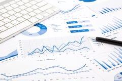 Relatórios azuis do gráfico e da carta na tabela do escritório