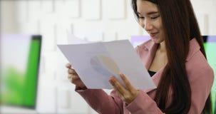 Relatórios de leitura asiáticos da mulher de negócio no escritório filme