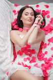 Related girl lying in rose petals. Royalty Free Stock Photos
